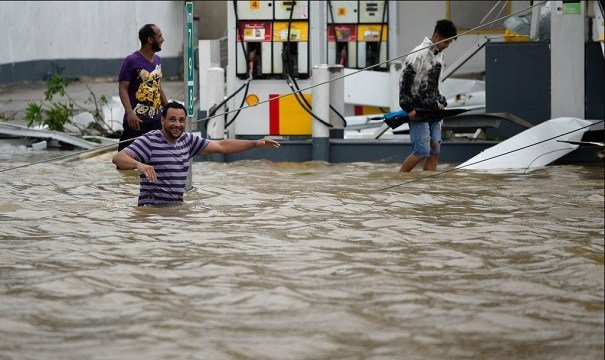 People walk next to a gas station flooded and damaged by the impact of Hurricane Maria.