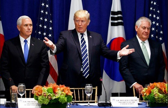 President Trump gestures for people to take their seat at a luncheon with South Korean President Moon Jae-in and Japanese Prime Minister Shinzo Abe.