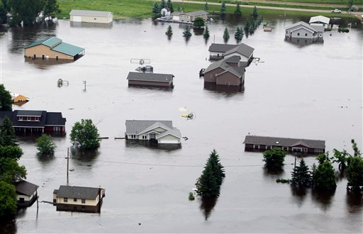 In this aerial photo flood waters from the Souris River continue to rise and consume neighborhoods in Burlington, N.D., Friday, June 24, 2011.