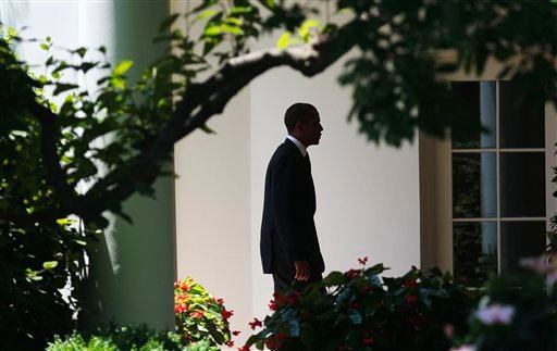 A silhouetted President Barack Obama walks back to the Oval Office of the White House in Washington, Friday, June, 24, 2011, following his arrival on Marine One helicopter.