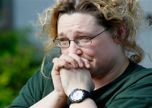 Leslie Dull holds back tears after looking from a distance at her flooded home, Saturday, June 25, 2011, in the Oak Park neighborhood of Minot, N.D. (AP Photo/Charles Rex Arbogast)