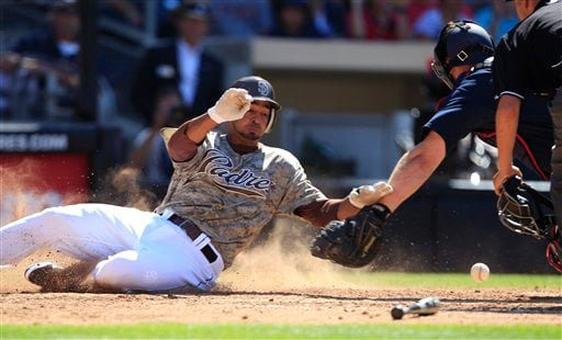 San Diego Padres' Jesus Guzman misses home plate as the ball get away from Atlanta Braves catcher David Ross in the eighth inning of a baseball game Sunday, June 26, 2011 in San Diego. (AP Photo/Lenny Ignelzi)