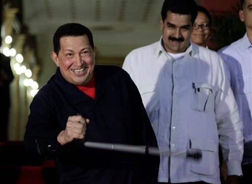 In this Thursday, June 2, 2011 Venezuela's President Hugo Chavez, left, holds a crutch as he welcomes Brazil's former President Luiz Inacio Lula da Silva, not in picture, at Miraflores presidential palace in Caracas, Venezuela.
