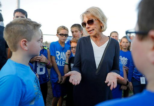 U.S. Secretary of Education Betsy DeVos talks with students during a high school football game between Eastern Hancock and Knightstown, Friday, Sept. 15, 2017, in Charlottesville, Ind. (AP Photo/Darron Cummings)