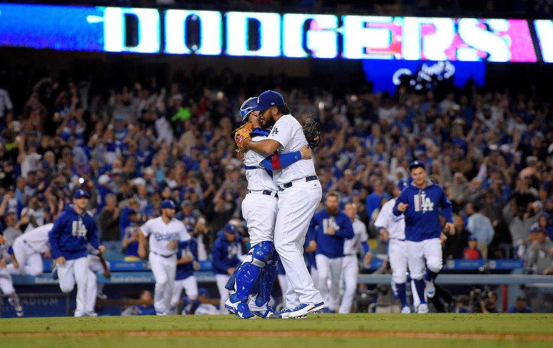 Los Angeles Dodgers relief pitcher Kenley Jansen, right, and catcher Yasmani Grandal celebrate the team's 4-2 win over the San Francisco Giants and clinch of the NL West title, after a baseball game Friday, Sept. 22, 2017, in Los Angeles. (AP Photo/Mark J