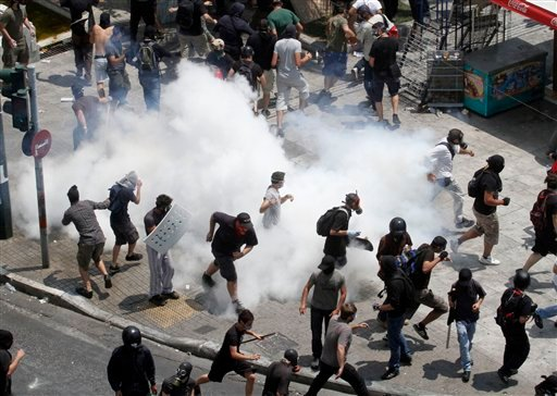 Demonstrators run away from tear gas during a demo in Athens on Tuesday June 28, 2011. (AP)