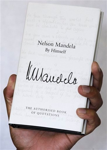 A copy of former South African president Nelson Mandela's newly released book, titled Nelson Mandela By Himself, is held up for a photograph in Johannesburg, South Africa, Monday, June 27, 2011.
