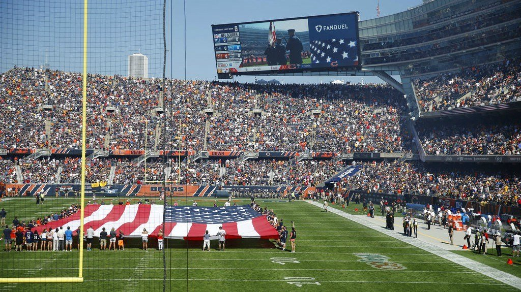 Fans watch the unfurled flag on the field during the national anthem before an NFL football game between the Chicago Bears and Pittsburgh Steelers Sunday. The Steelers players did not come out to the field during the anthem. (AP/Charles Rex Arbogast)