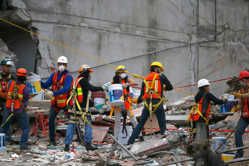 Search and rescue workers remove rubble a bucket at a time while standing on the debris of a felled office building brought down by a 7.1-magnitude earthquake, in the Roma Norte neighborhood of Mexico City, Sunday, Sept. 24, 2017. (AP Photo/Marco Ugarte)