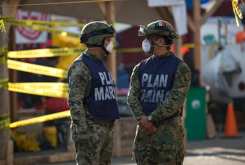 Mexican Marine soldiers stand guard at the zone where a felled office building brought down by a 7.1-magnitude earthquake, in the Roma Norte neighborhood of Mexico City, Sunday, Sept. 24, 2017. (AP Photo/Moises Castillo)