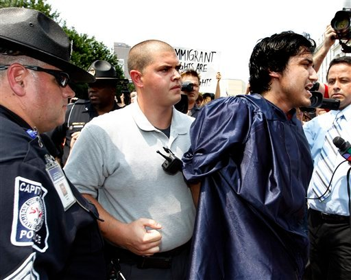 A protester is taken into custody during a rally protesting Georgia's new immigration law on the Capitol steps Tuesday, June 28, 2011 in Atlanta.