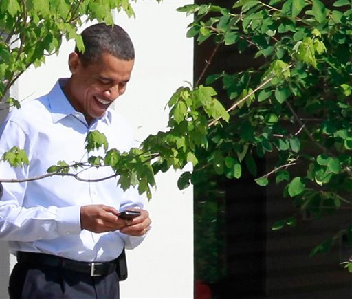 FILE - In this June 3, 2010 file photo, President Barack Obama uses his BlackBerry e-mail device as he walks at Sidwell Friends school in Bethesda, Md.