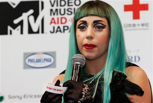 "Lady Gaga speaks while holding a ""We pray for Japan"" wrist band during a press conference to promote MTV Video Music Aid Japan in Tokyo Thursday, June 23, 2011."