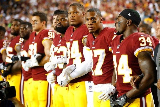 Member of the Washington Redskins stand arm in arm during the playing of the National Anthem .