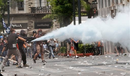 A protester uses a fire extinguisher against police at Syntagma Square in front of the Greek Parliament in central Athens, Wednesday, June 29, 2011. (AP Photo/Petros Karadjias)