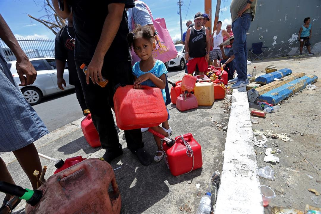Abi de la Paz de la Cruz, 3, holds a gas can as she waits in line with her family, to get fuel from a gas station, in the aftermath of Hurricane Maria, in San Juan, Puerto Rico, Monday, Sept. 25, 2017. (AP Photo/Gerald Herbert)