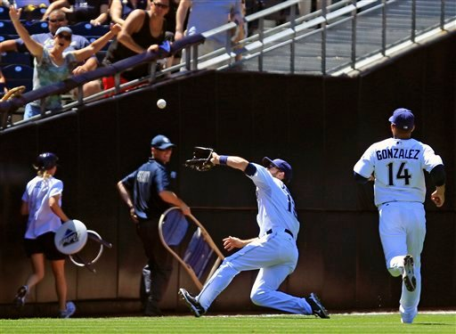 Padres left fielder Chris Denorfia, second from right, makes a sliding catch on a fly ball hit by Kansas City Royals' Melky Cabrera down the left field line in the 8th inning of a baseball game on June 29, 2011, in San Diego. (AP Photo/Lenny Ignelzi)