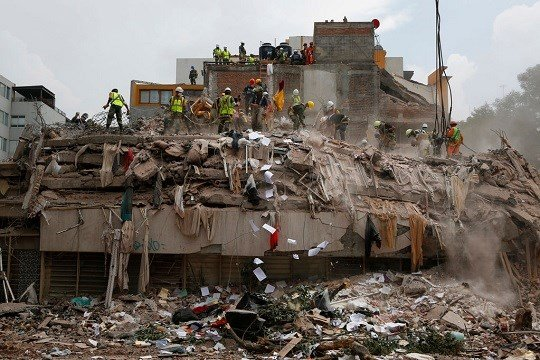 Workers shovel papers and debris off the top of the rubble of a building that collapsed in last week's 7.1 magnitude earthquake.
