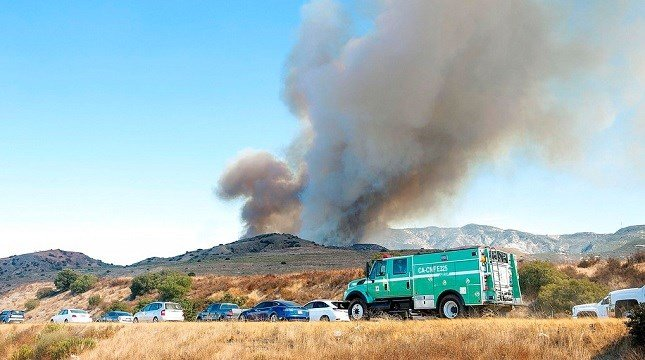 Authorities head to fight a wildfire near the Riverside County line in Anaheim Hills, Calif.