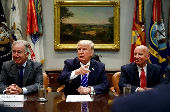 Rep. Richard Neal, D-Mass., left, and Rep. Kevin Brady, R-Texas, right, listen as President Donald Trump speaks.