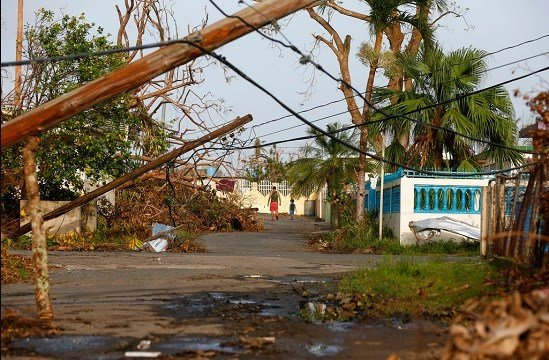 A man and child walk down street strewn with debris and downed power lines in the aftermath of Hurricane Maria, in Yabucoa, Puerto Rico.
