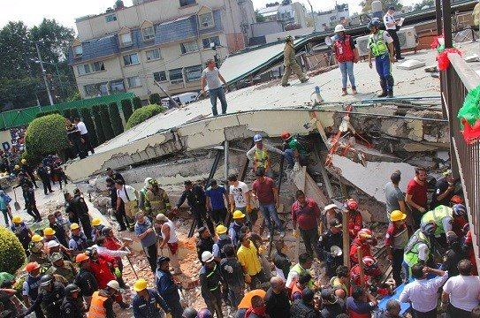 Rescue workers search for children trapped inside the collapsed Enrique Rebsamen school in Mexico City.