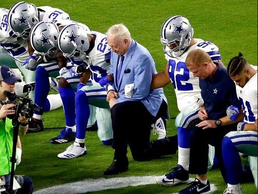 The Dallas Cowboys, led by owner Jerry Jones, center, take a knee prior to the national anthem.