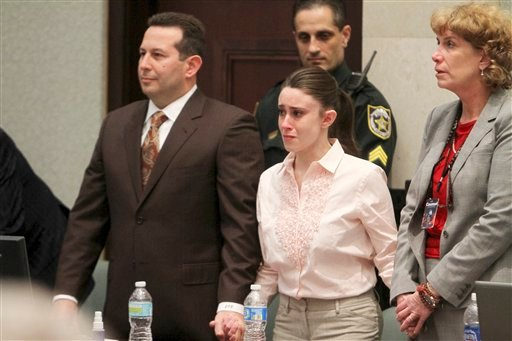 Casey Anthony holds hands with her defense attorneys, Jose Baez, left, and Dorothy Clay Sims, as they listen to the verdict, not guiity on murder charges, at the Orange County Courthouse in Orlando, Fla., Tuesday, July 5, 2011.