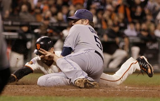 San Francisco Giants' Andres Torres, left, is tagged out at home plate by San Diego Padres relief pitcher Chad Qualls, right, on a fielder's choice during the seventh inning of their baseball game in San Francisco July 5, 2011. (AP Photo/Eric Risberg)