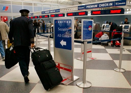 In this Nov. 24, 2004 file photo, a United Airlines pilot walks to security check point at O'Hare International Airport, in Chicago. (AP Photo/Nam Y. Huh, file)