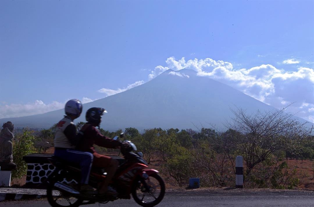 Motorists ride past by with Mount Agung volcano seen in the background in Karangasem, Bali, Indonesia, Thursday, Sept. 28, 2017.  (AP Photo/Firdia Lisnawati)