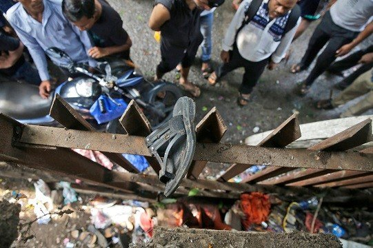 A slipper of an injured commuter is seen stuck on the railing of a pedestrian bridge where a stampede took place at the Elphinstone station, in Mumbai, India.
