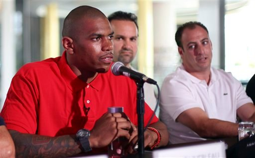 Former Ohio State football player Terrelle Pryor, left, as members of his agent Drew Rosenhaus' staff look oon during a news conference. (AP)