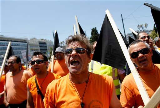 State-employed fruit and vegetable market employees chant slogans during a protest against the Greek government's austerity measures and privatization plans, in Athens, on Friday, June 10, 2011.