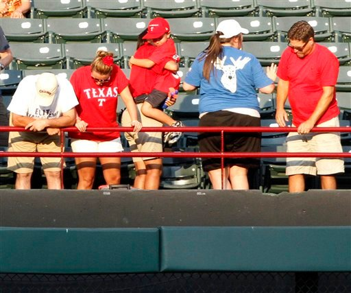 People look over the outfield railing after baseball fan Shannon Stone fell while trying to grab a ball in the second inning of the baseball game between the Texas Rangers and the Oakland Athletics Thursday, July 7, 2011, in Arlington, Texas.