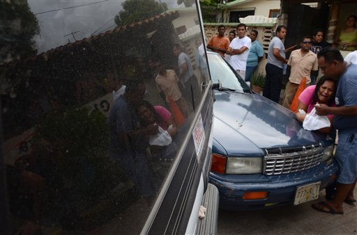 An unidentified woman weeps for her relatives at the scene where gunmen attacked a tow truck business in the Pacific resort city of Acapulco, Mexico Friday July 8, 2011. (AP Photo/Bernandino Hernandez)