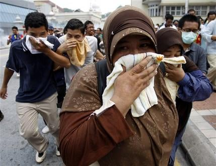 Malaysian activists from Coalition for Clean and Fair Elections cover themselves with towels as they run away from tear gas fired by police during a rally calling for electoral reforms in Kuala Lumpur, Malaysia July 9, 2011. (AP Photo/Lai Seng Sin)
