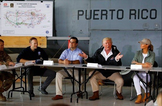 President Donald Trump and first lady Melania Trump participate in a briefing on hurricane recovery efforts with first responders at Luis Muniz Air National Guard Base.