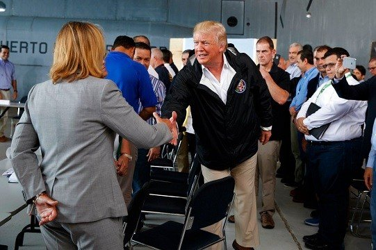 President Donald Trump shakes hands with San Juan Mayor Carmen Yulin Cruz during a briefing on hurricane recovery efforts.