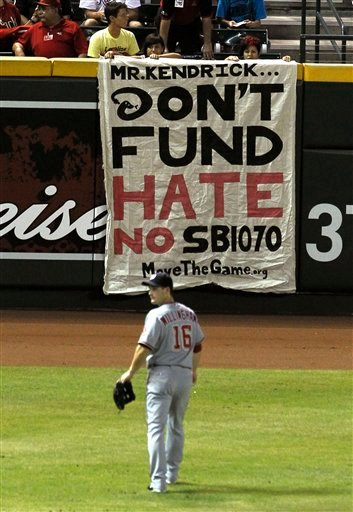 In this Aug. 2, 2010, file photo, Washington Nationals' Josh Willingham (16) walks toward the outfield as play is stopped as protesters hang a banner against the new Arizona immigration law SB1070, the Arizona Diamondbacks ownership and moving the 2011.