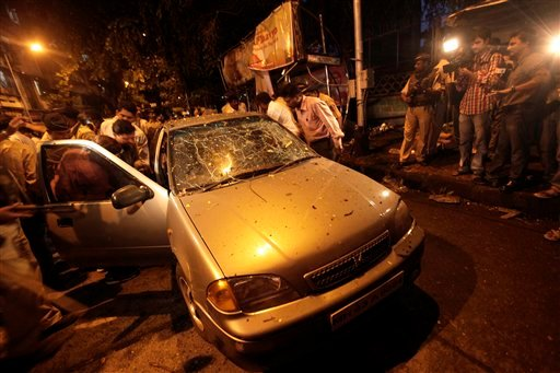 Police officers inspect the site of an explosion at Dadar in Mumbai, India, Wednesday, July 13, 2011. (AP Photo/Rajanish Kakade)