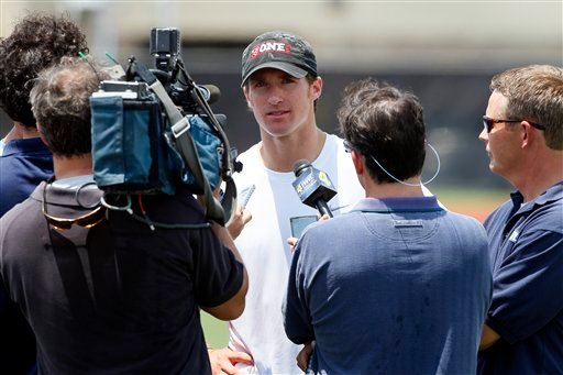 New Orleans Saints quarterback Drew Brees, center, speaks with reporters after a player-organized practice at Tulane University in New Orleans, Wednesday, June 15, 2011.