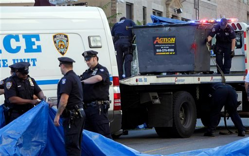 Police officers prepare to remove a dumpster, right, that is part of an investigation about a missing 8-year old boy in the Brooklyn borough of New York, Wednesday, July 13, 2011.