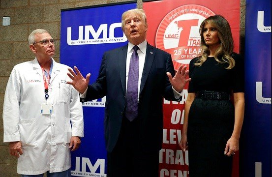 President Donald Trump talks as first lady Melania Trump and surgeon Dr. John Fildes listens at the University Medical Center.