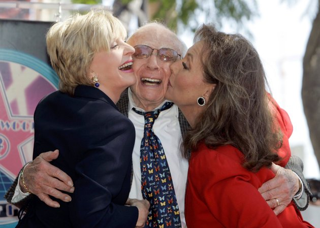 FILE - In this March 7, 2008 file photo, writer/producer Sherwood Schwartz receives a kiss from actresses Florence.
