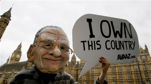 A demonstrator from Avaaz, a global campaigning group, wearing a Rupert Murdoch head, hold banners in front of Parliament in London, Wednesday, July 13, 2011.