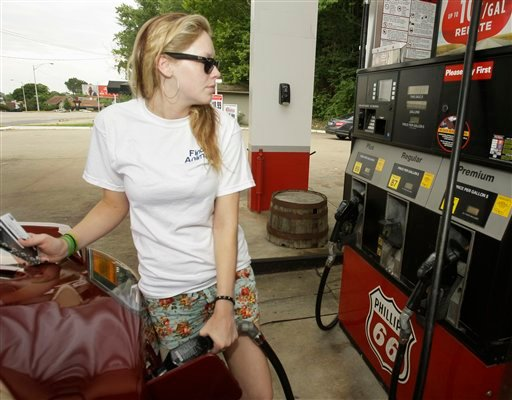 In this June 22, 2011 photo, Susan Bridges pumps gas into her car at a Little Rock, Ark., Conoco Phillips station. Companies paid less for raw materials and factory goods in June. (AP Photo/Danny Johnston)