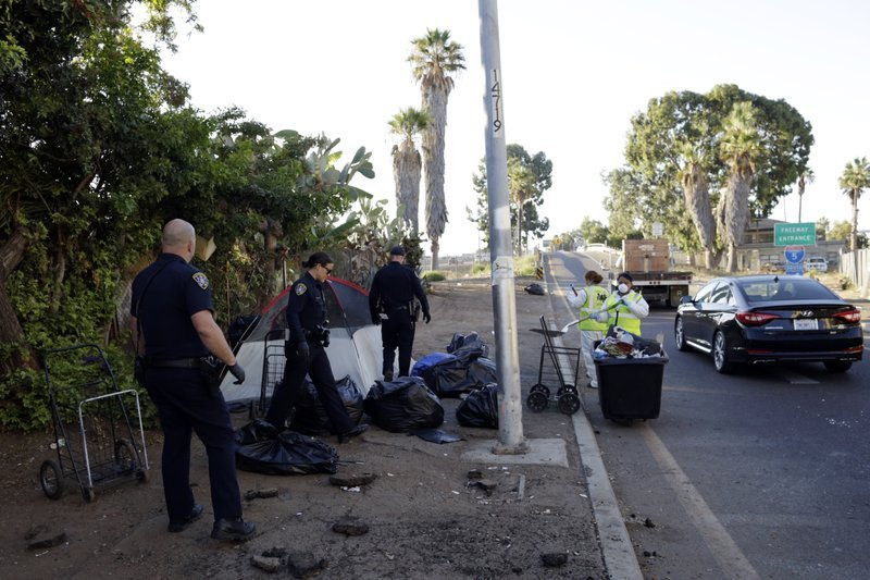 In this Sept. 25, 2017 file photo, police officers remove a tent left by the homeless during efforts to sanitize neighborhoods to control the spread of hepatitis A, in San Diego.