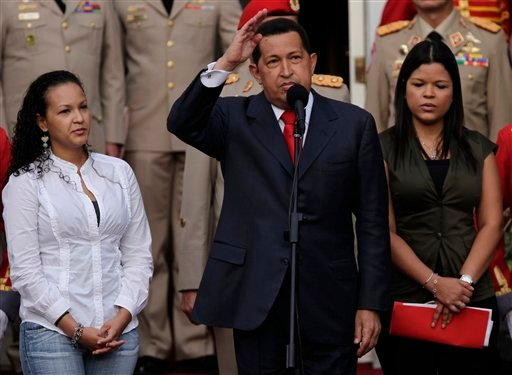 Venezuelan President Hugo Chavez, flanked by his daughters Rosa Virginia, right, and Gabriela, gestures after he announced he will return to Cuba Saturday to begin a new phase of cancer treatment.