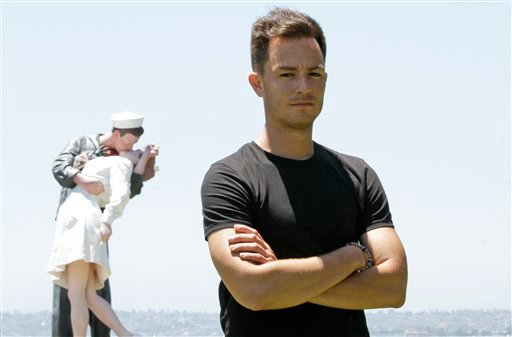 Sean Sala poses in front of a statue of a Navy sailor kissing a nurse Thursday, July 14, 2011, in San Diego. Sala, a former sailor, is organizing a military contingent of hundreds of former and active-duty troops to lead San Diego's Gay Pride March. (AP)